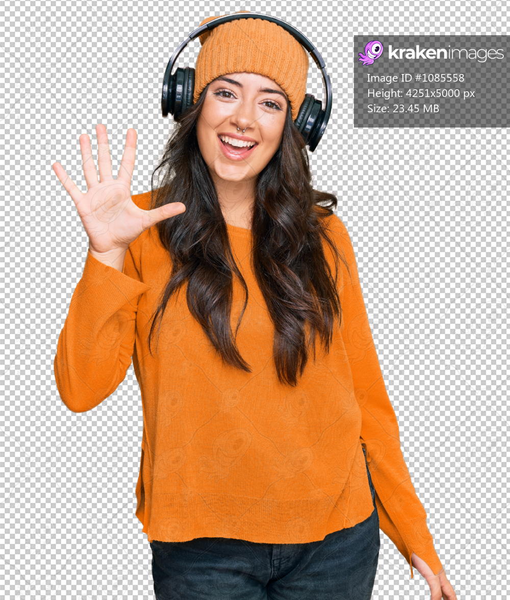 Beautiful brunette young woman listening to music using headphones showing and pointing up with fingers number five while smiling confident and happy.