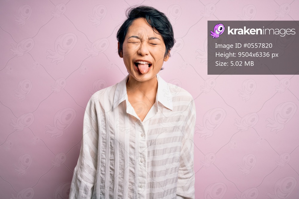 Young beautiful asian girl wearing casual shirt standing over isolated pink background sticking tongue out happy with funny expression. Emotion concept.