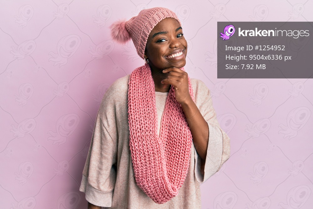 Young african american woman wearing wool hat and winter scarf smiling looking confident at the camera with crossed arms and hand on chin. thinking positive.