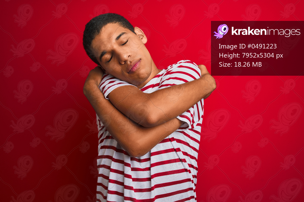 Young handsome arab man wearing striped t-shirt over isolated red background Hugging oneself happy and positive, smiling confident. Self love and self care