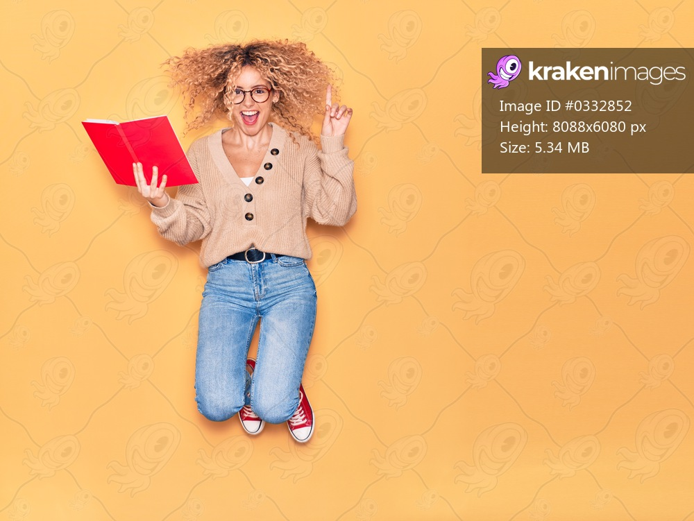 Young beautiful curly student girl wearing glasses smiling happy. Jumping with smile on face reading book over isolated yellow background.