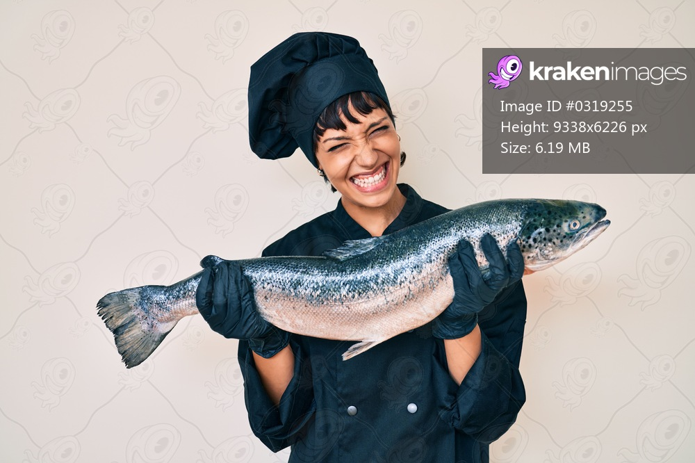 Beautiful brunettte woman professional chef holding fresh salmon fish smiling and laughing hard out loud because funny crazy joke.