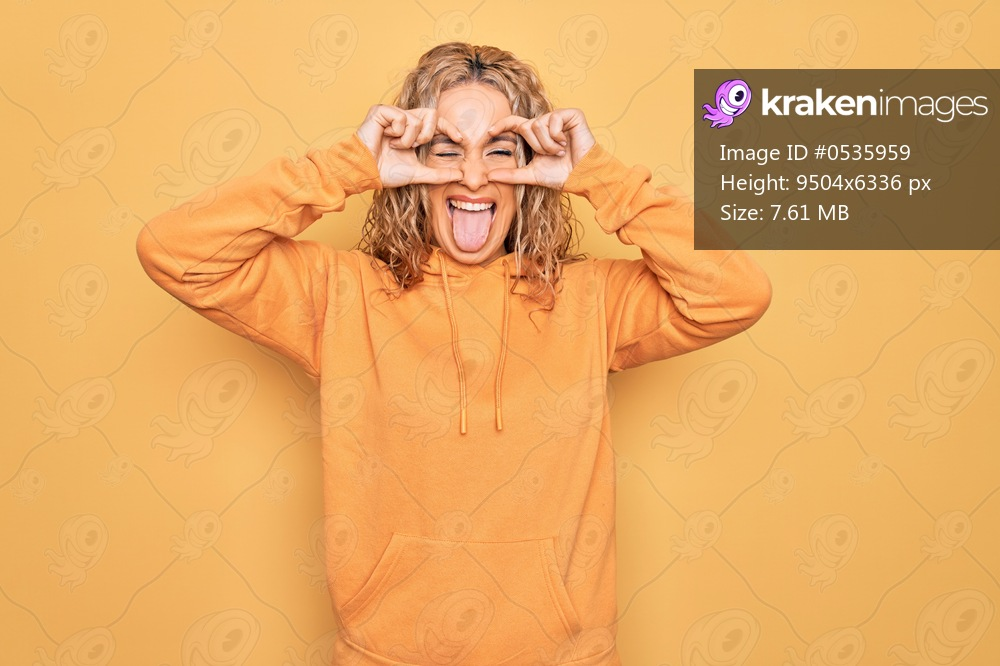 Young beautiful blonde sporty woman wearing casual sweatshirt over yellow background doing ok gesture like binoculars sticking tongue out, eyes looking through fingers. Crazy expression.