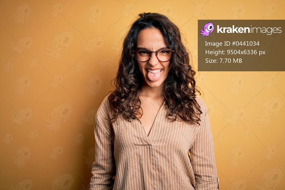 Beautiful woman with curly hair wearing striped shirt and glasses over yellow background sticking tongue out happy with funny expression. Emotion concept.