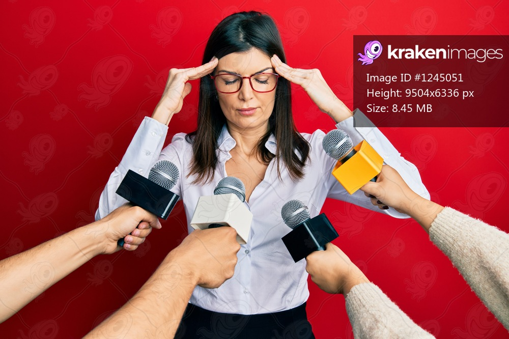 Young hispanic woman being interviewed for journalist hands with microphone with hand on head, headache because stress. suffering migraine.