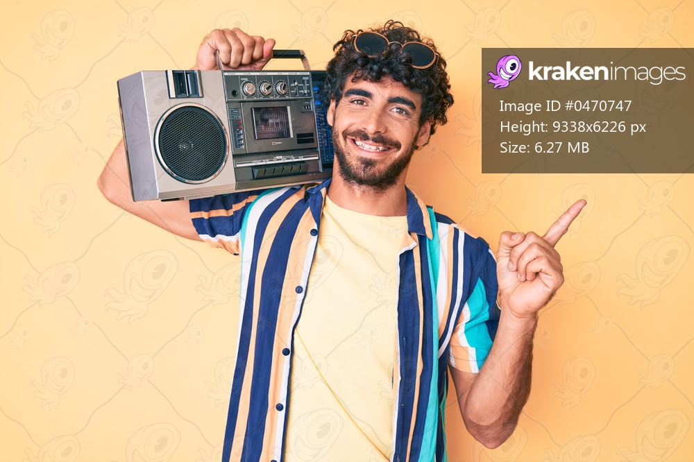 Handsome young man with curly hair and bear holding boombox, listening to music wearing summer look smiling happy pointing with hand and finger to the side
