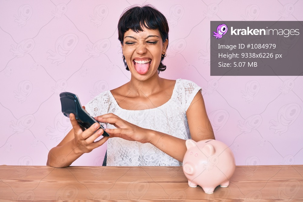 Beautiful brunettte woman caculating money savings sticking tongue out happy with funny expression.