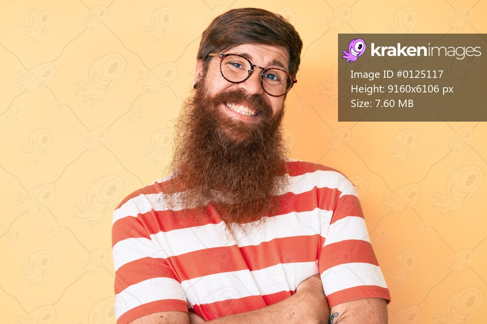 Handsome young red head man with long beard wearing casual clothes and glasses happy face smiling with crossed arms looking at the camera. positive person.