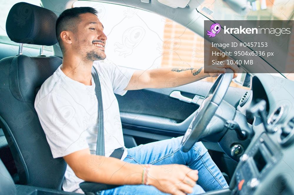 Young hispanic man smiling happy driving car.