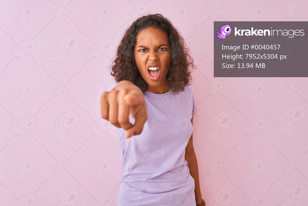 Young brazilian woman wearing t-shirt standing over isolated pink background pointing displeased and frustrated to the camera, angry and furious with you