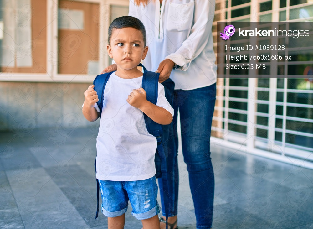 Adorable latin student boy and mom waiting at school.