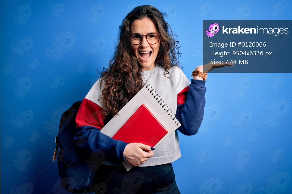Young beautiful student woman with curly hair wearing backpack holding book and notebook very happy and excited, winner expression celebrating victory screaming with big smile and raised hands