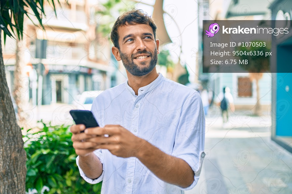 Handsome man with beard wearing casual white shirt on a sunny day smiling happy outdoors using smartphone