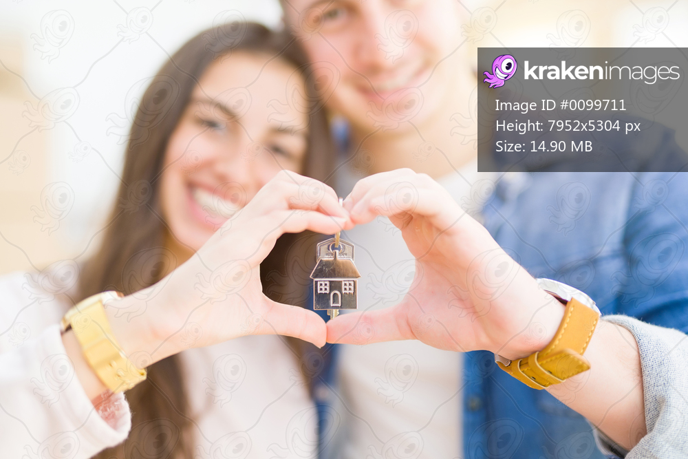 Beautiful young couple hugging in love and showing keys of new house, smiling happy moving to a new apartment