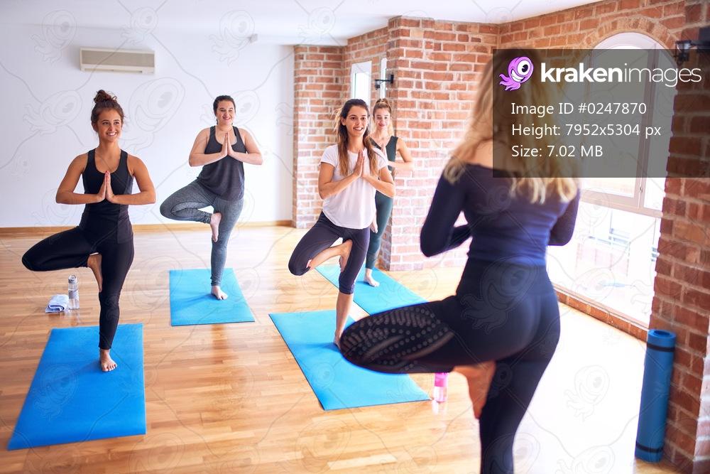 Young beautiful group of sportswomen practicing yoga. Coach teaching tree pose to sporty women at gym