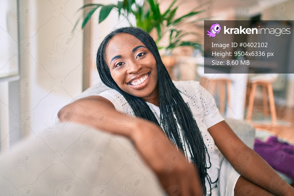 Young african american woman smiling happy sitting on the sofa at home