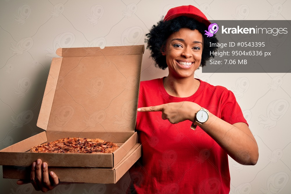 Young African American afro delivery woman with curly hair holding box with Italian pizza very happy pointing with hand and finger