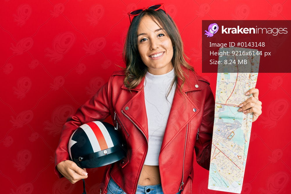 Young brunette woman holding motorcycle helmet and city map smiling with a happy and cool smile on face. showing teeth.