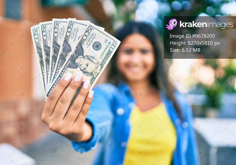 Young latin woman smiling happy holding usa dollars banknotes at city.