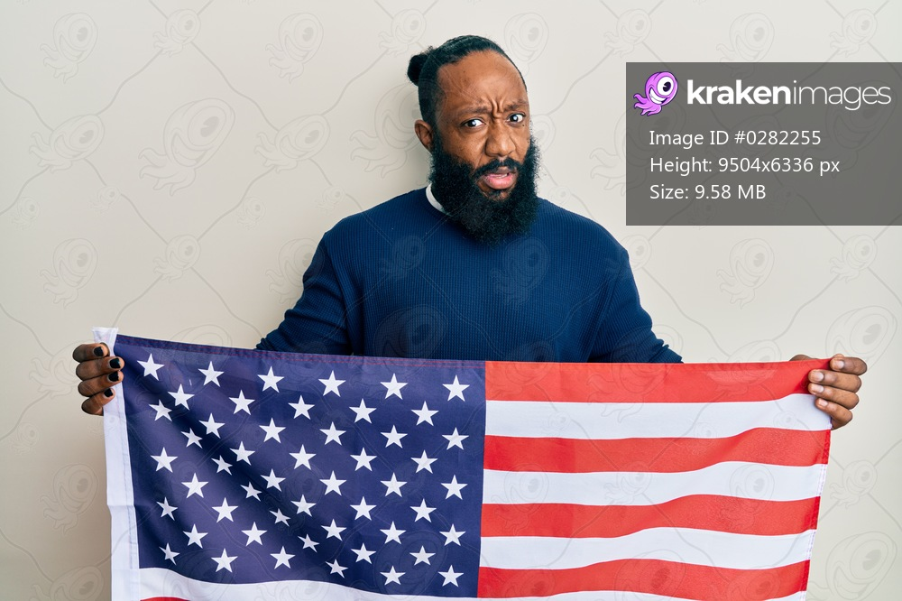Young african american man holding united states flag clueless and confused expression. doubt concept.