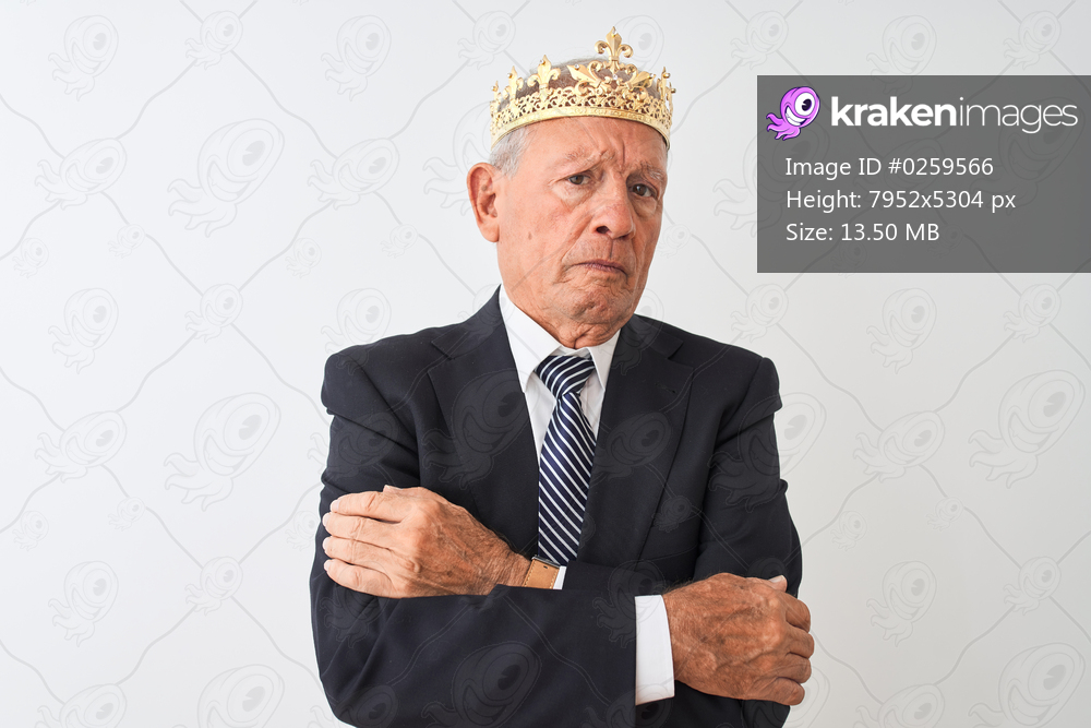 Senior grey-haired businessman wearing crown king over isolated white background skeptic and nervous, disapproving expression on face with crossed arms. Negative person.