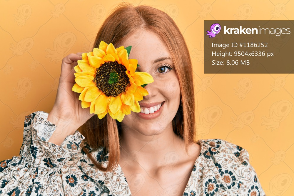 Young irish woman holding sunflower over eye looking positive and happy standing and smiling with a confident smile showing teeth