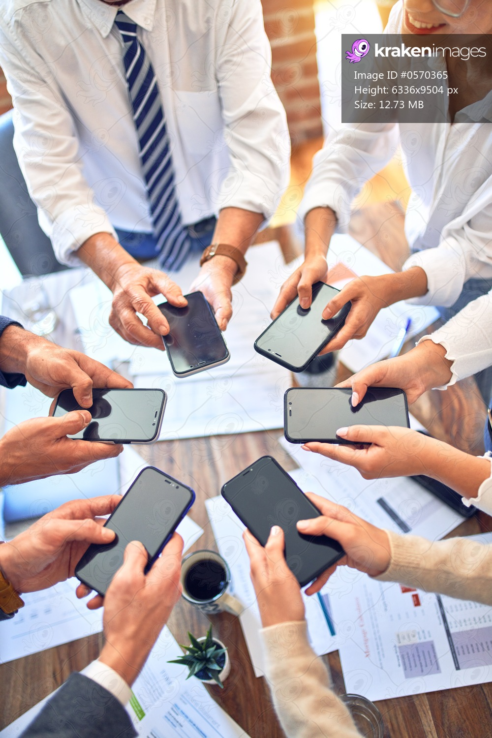 Group of business workers standing with hands together using smartphone doing symbol at the office
