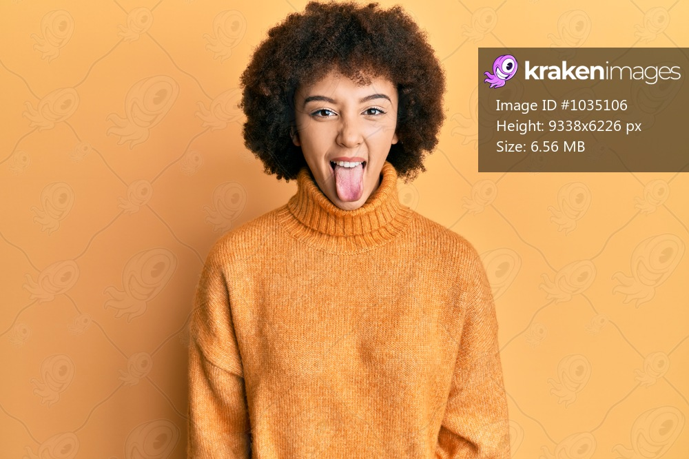 Young hispanic girl wearing wool winter sweater sticking tongue out happy with funny expression. emotion concept.