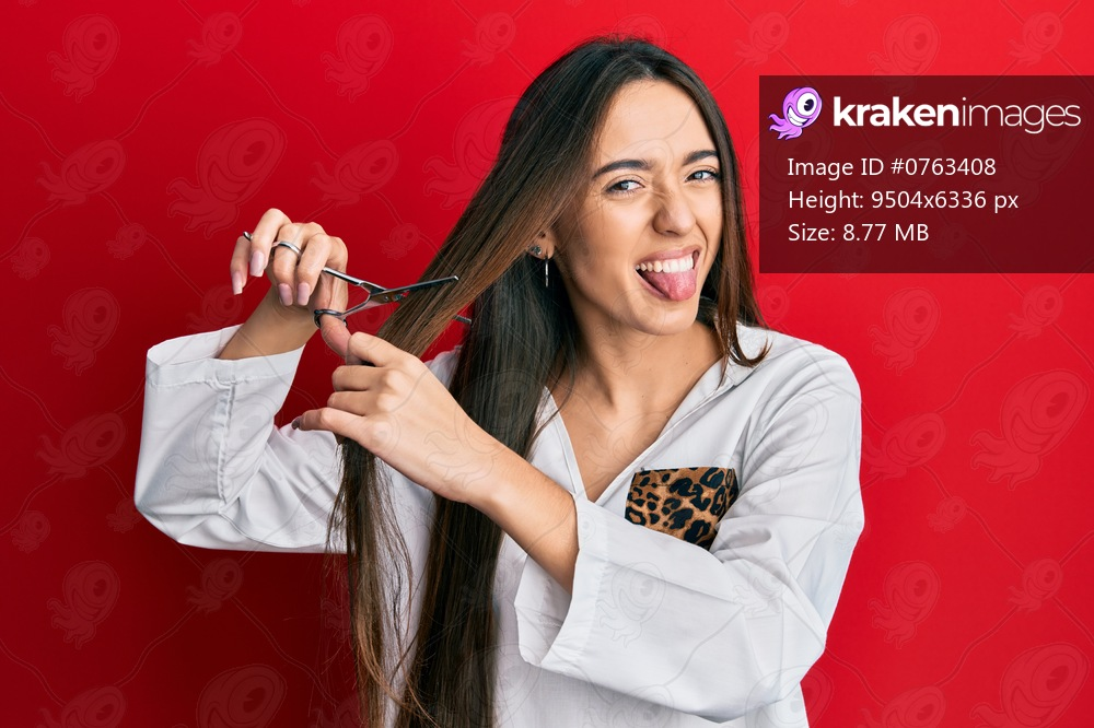Young hispanic girl cutting hair using scissors sticking tongue out happy with funny expression.