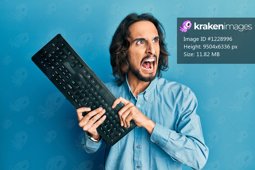 Young hispanic man holding keyboard angry and mad screaming frustrated and furious, shouting with anger. rage and aggressive concept.
