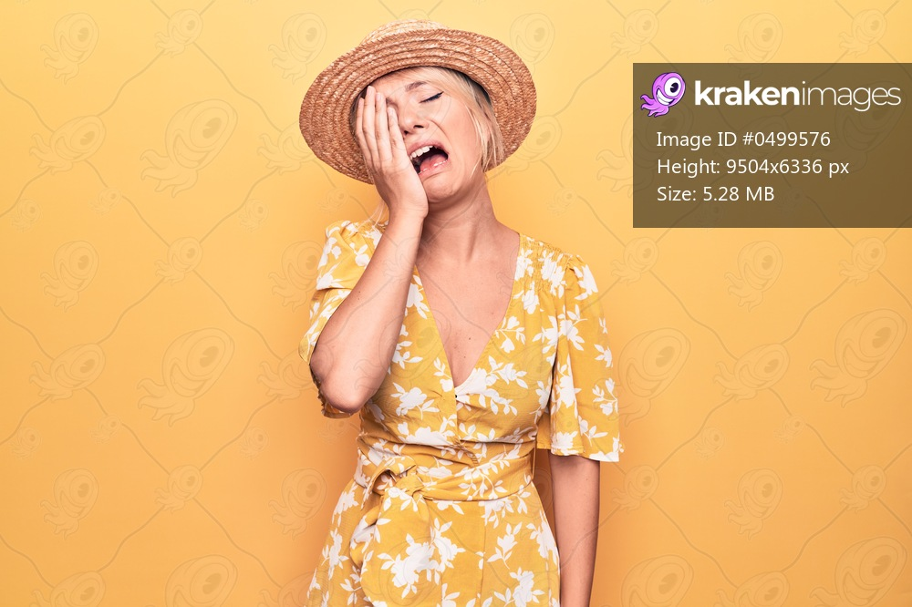 Beautiful blonde woman on vacation wearing summer hat and dress over yellow background Yawning tired covering half face, eye and mouth with hand. Face hurts in pain.