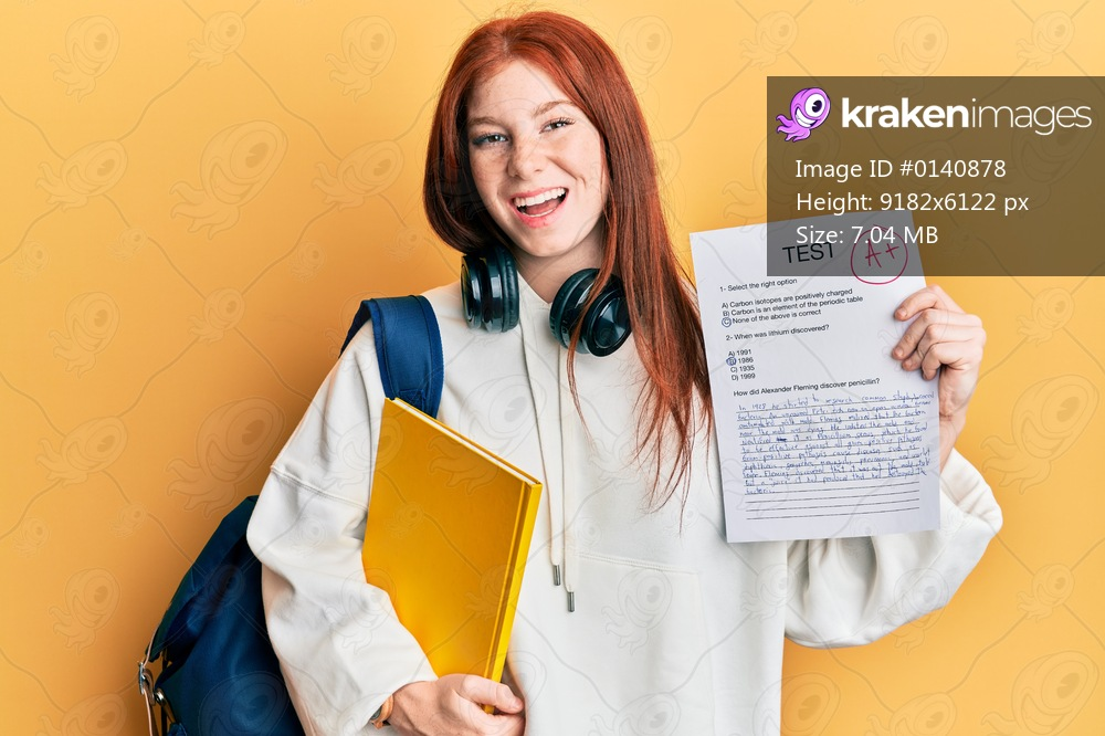 Young red head girl wearing student backpack holding passed test smiling and laughing hard out loud because funny crazy joke.