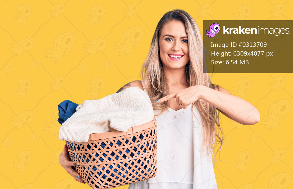 Young beautiful blonde woman holding laundry basket smiling happy pointing with hand and finger