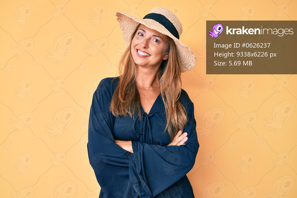 Middle age hispanic woman wearing summer hat happy face smiling with crossed arms looking at the camera. positive person.