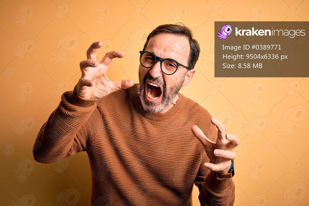Middle age hoary man wearing brown sweater and glasses over isolated yellow background Shouting frustrated with rage, hands trying to strangle, yelling mad