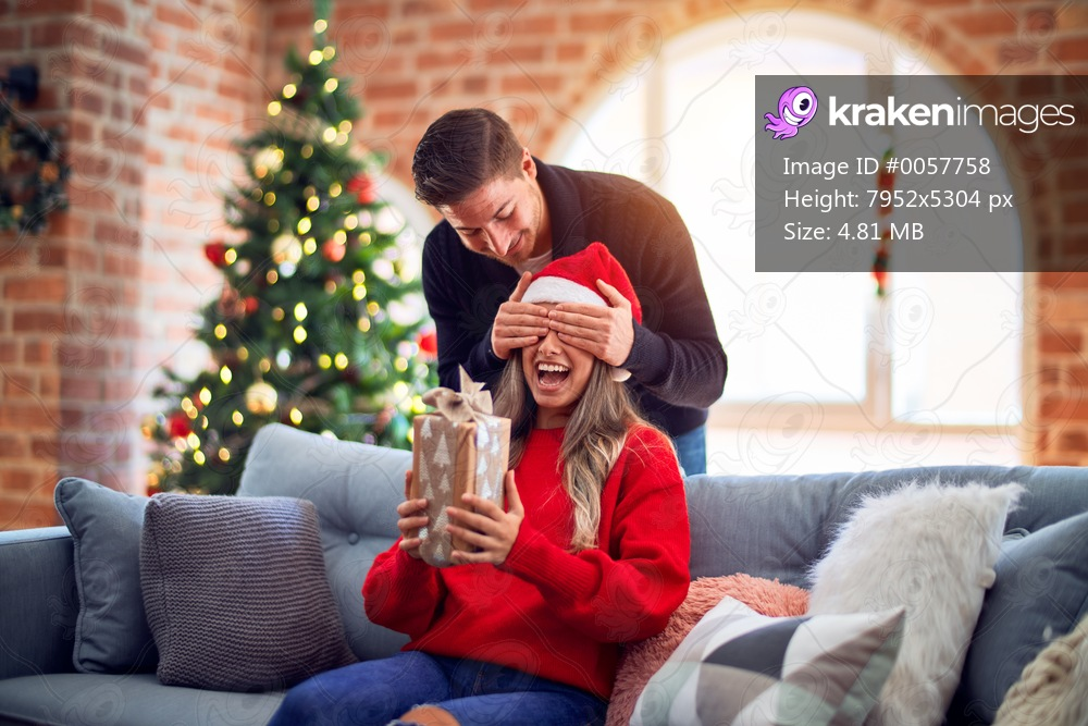 Young beautiful couple smiling happy and confident. Man covering eyes of woman surpise her with gift around christmas tree at home