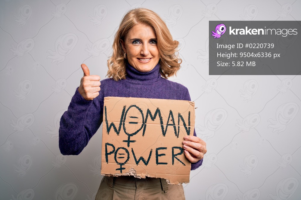 Middle age beautiful blonde woman asking for women rights holding banner happy with big smile doing ok sign, thumb up with fingers, excellent sign