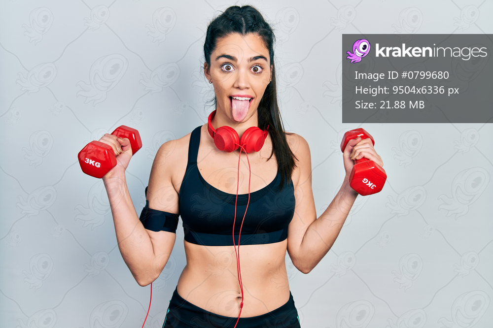 Young hispanic girl wearing sportswear using dumbbells sticking tongue out happy with funny expression.
