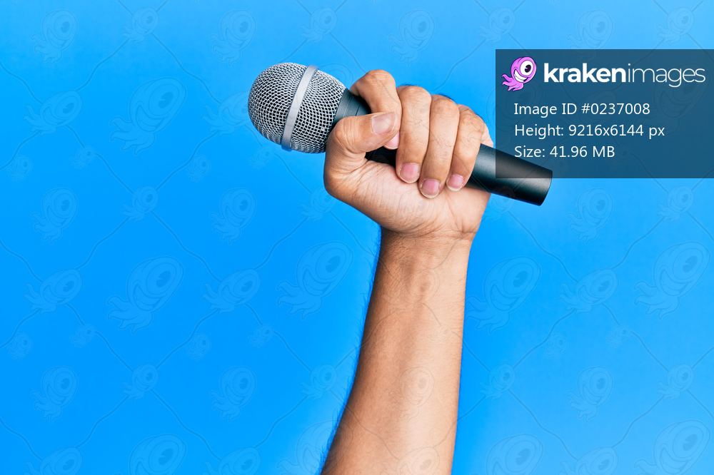 Hand of hispanic man holding microphone over isolated blue background.