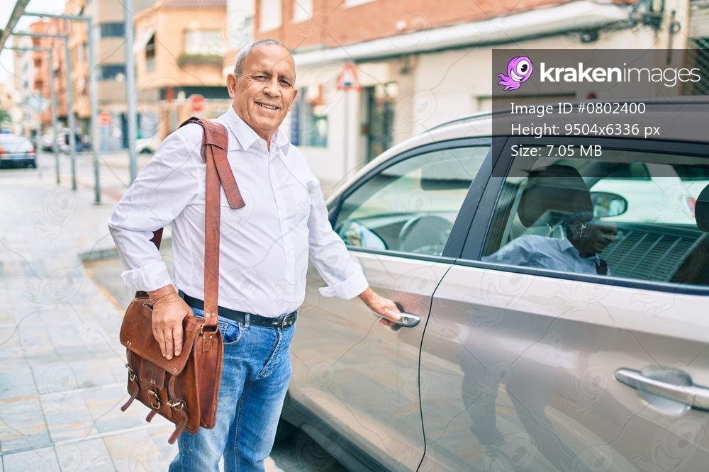 Senior man smiling happy opening car at the city.