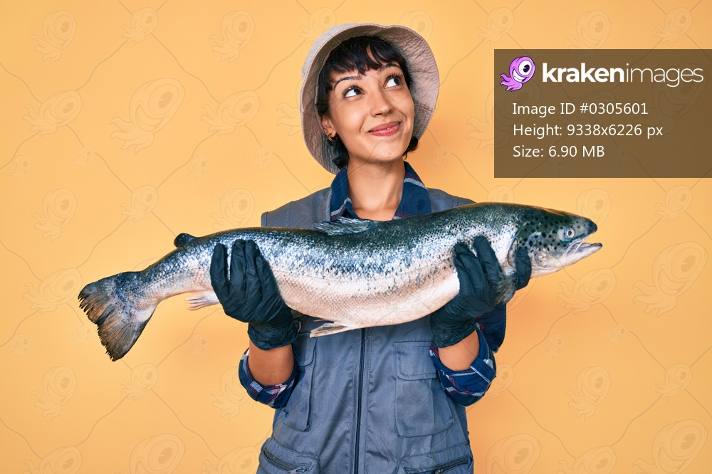 Beautiful brunettte fisher woman showing raw salmon smiling looking to the side and staring away thinking.