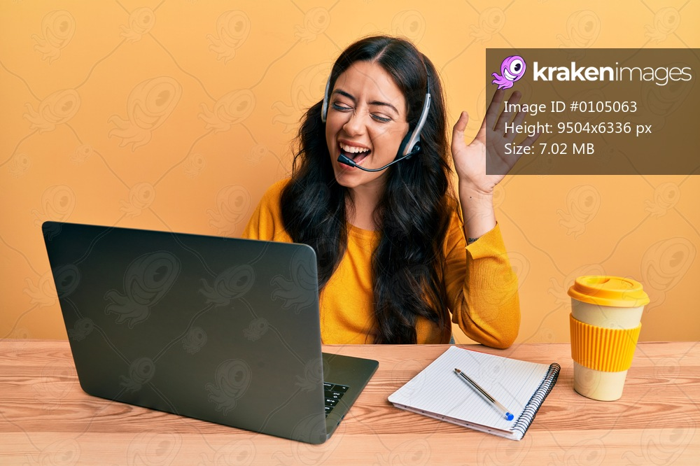 Beautiful brunette young woman wearing call center agent headset smiling and laughing hard out loud because funny crazy joke.