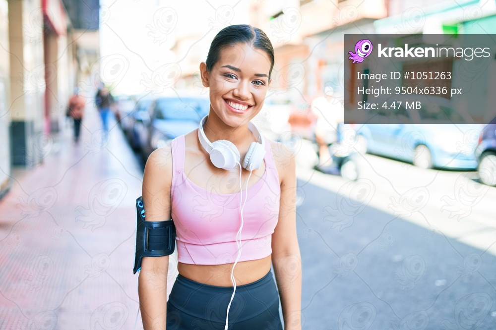 Young beautiful hispanic sport woman wearing runner outfit and headphones smiling happy at the town
