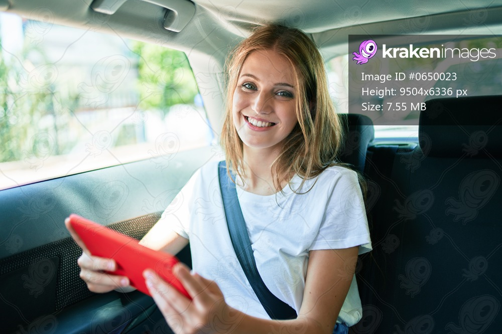 Young beautiful blonde woman smiling happy sitting at the car using tablet.