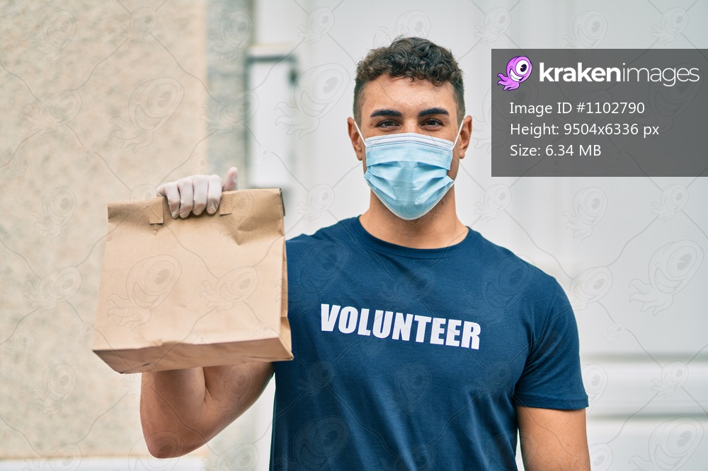 Young hispanic volunteer man wearing medical mask holding delivery bag at the city.