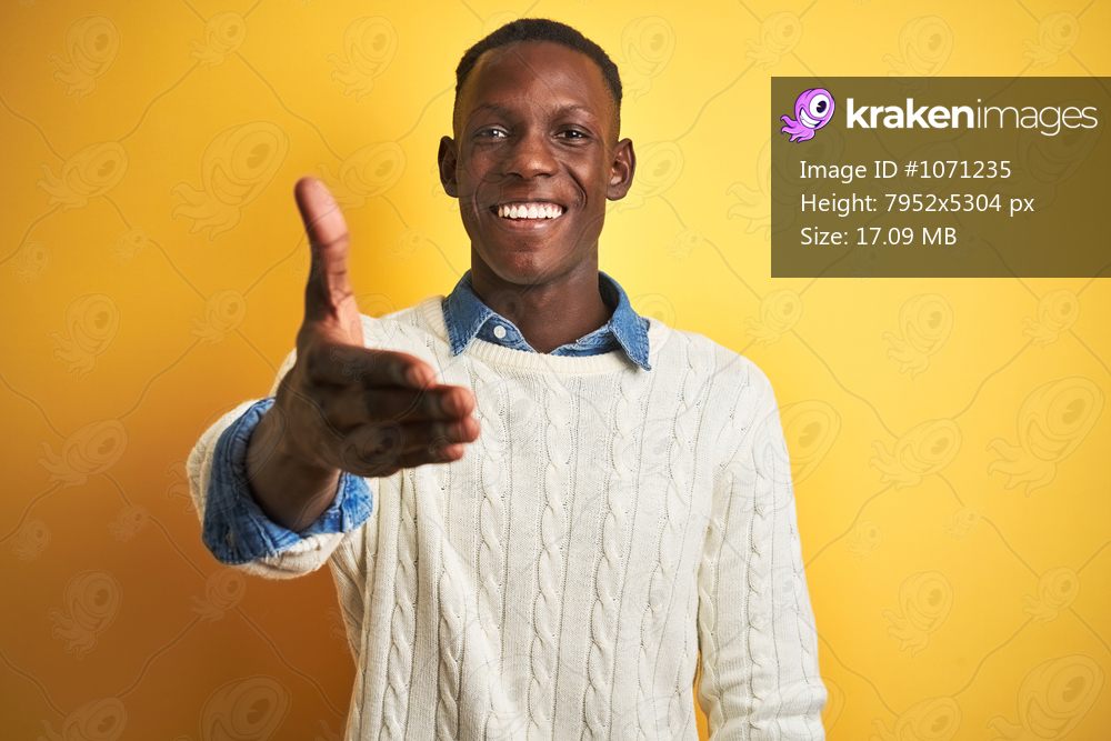African american man wearing denim shirt and white sweater over isolated yellow background smiling friendly offering handshake as greeting and welcoming. Successful business.