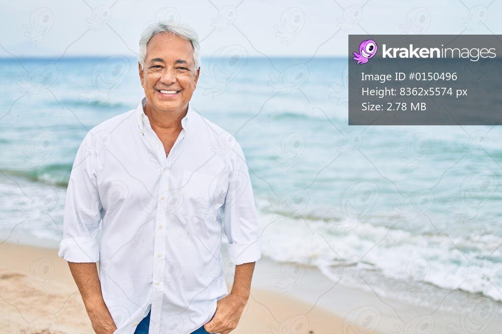 Handosme hispanic man with grey hair smiling happy at the beach, enjoying holidays on summer