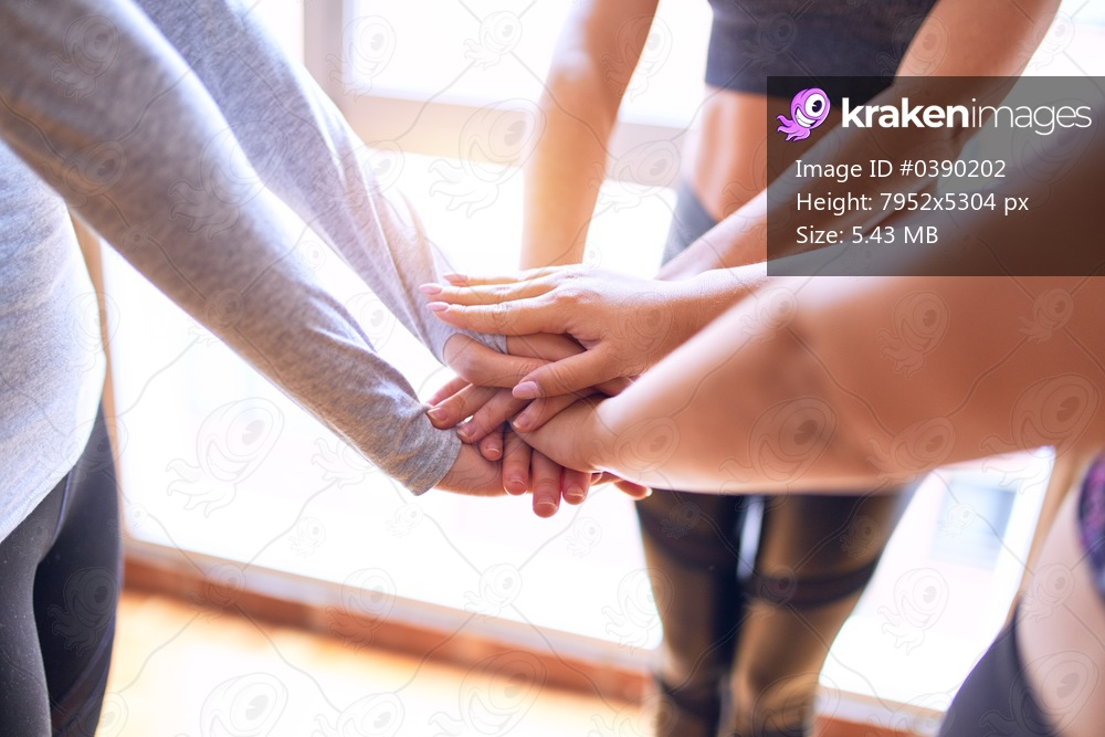 Young beautiful group of sportswomen standing shaking hands after class of yoga at gym