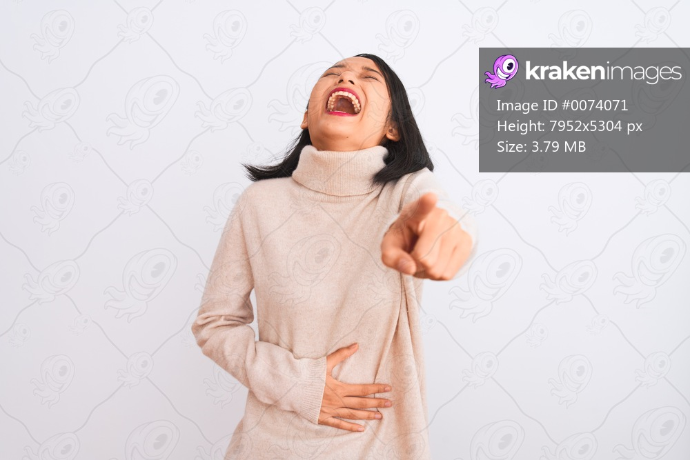 Young chinese woman wearing turtleneck sweater standing over isolated white background laughing at you, pointing finger to the camera with hand over body, shame expression