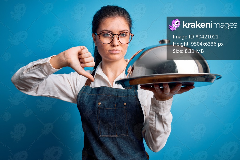 Young beautiful waitress woman with blue eyes holding tray with dome over isolated background with angry face, negative sign showing dislike with thumbs down, rejection concept